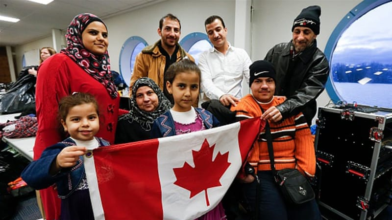 A Syrian refugee family, sponsored by a local group called Ripple Refugee Project, pose for photos in Toronto [Getty]