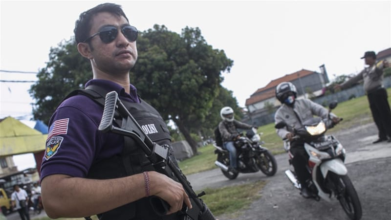 Indonesian policemen check motorcyclists during a roadblock to thwart an anticipate terrorism threat in Bali, Indonesia [EPA]