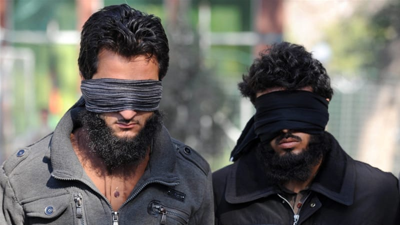 Afghan security officers escort two alleged ISIL members in Nangarhar province, Afghanistan [EPA]