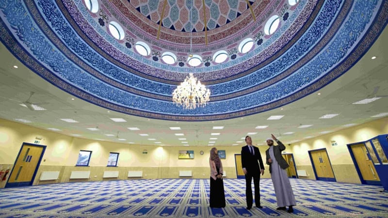 David Cameron speaks with imam Qari Asim, right, and Shabana Muneer, a member of the mosque's women's group, as he visits the Makkah Masjid Mosque in Leeds [Reuters]