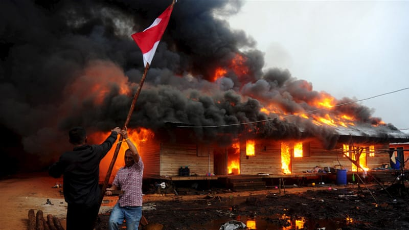 Men remove an Indonesian flag as a Gafatar sect compound burns after being set ablaze by villagers [Jessica Helena Wuysang/Antara]