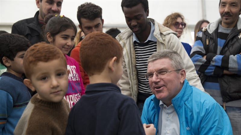 IOC President Thomas Bach,  chats with children during his visit at a refugee camp in Athens [Petros Giannakouris/AP]