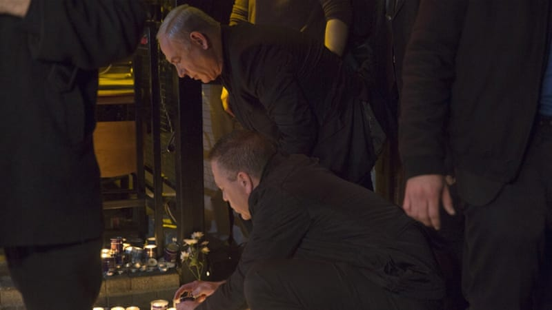 Israeli PM Benjamin Netanyahu lights a candle during a visit to the scene of shooting incident in Tel Aviv [Heidi Levine/Pool/Reuters]