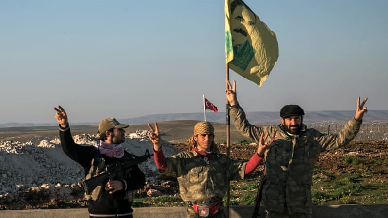 YPG members make a V-sign next to poster of Abdullah Ocalan, jailed Kurdish leader, and a Turkish army tank in the background in Esme village in Aleppo province, Syria. [AP]