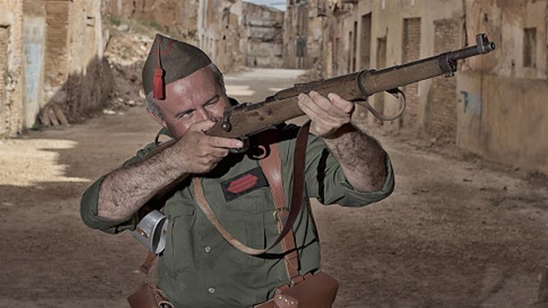 A Spanish Civil War re-enactor aiming his rifle [Getty]