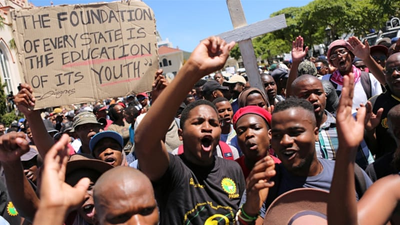 Students protest outside parliament before Finance Minister Pravin Gordhan's medium-term budget speech in Cape Town [Reuters]