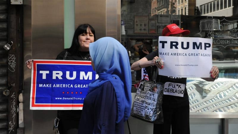 A woman wearing a Muslim headscarf walks past people holding Trump signs before the start of the annual Muslim Day Parade in the Manhattan borough of New York City [Reuters]