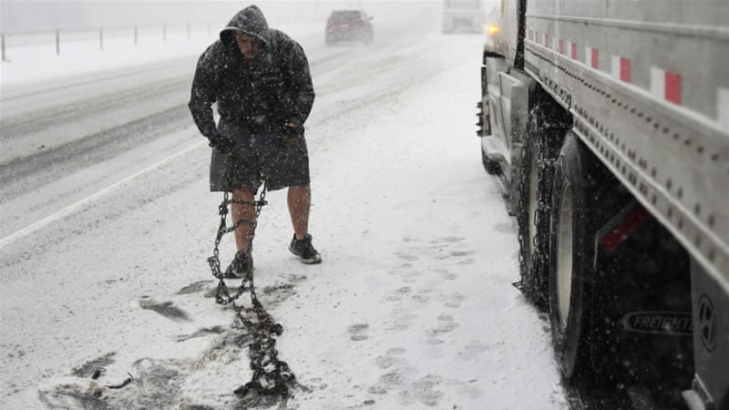 Lorry driver Tim Swartz, wearing shorts, stops to fit snow chains on Interstate 70, Colorado, US [Getty Images]