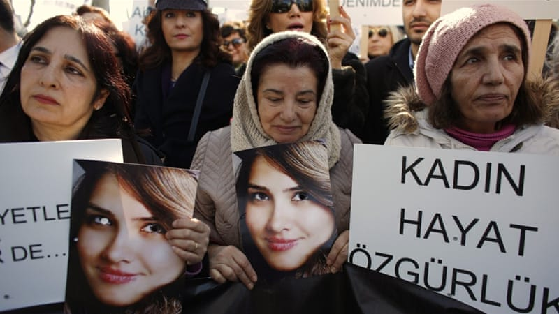 Women walk holding pictures of Ozgecan Arslan, a student who was raped and murdered, during a protest against domestic violence  [File: Murad Sezer/Reuters]-