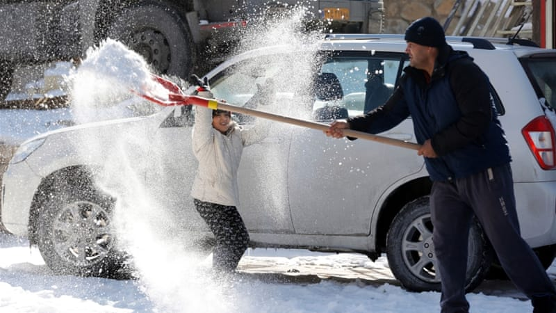 Work for him, fun for her. Clearing snow in Rude Hen, northern Iran  [EPA]
