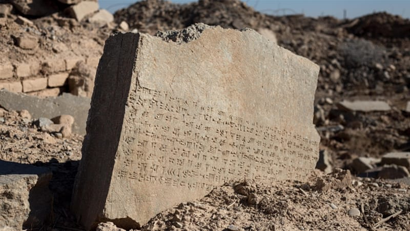 Much of Nimrud is nothing but a huge field of rubble dotted by chunks of stone with cuneiform writing and the odd murd brick wall [John Beck/Al Jazeera]