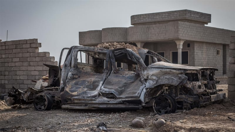 The remains of an ISIL lorry bomb, which was shot with a tank shell by Iraqi troops  [John Beck/Al Jazeera]