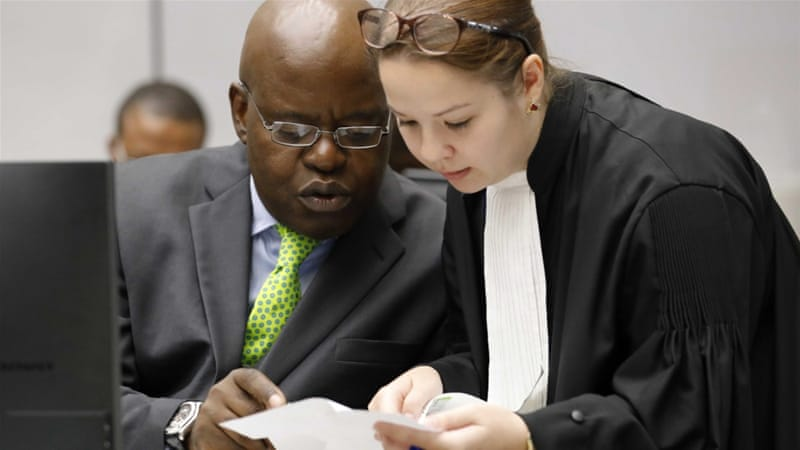 Fidele Babala Wandu, left, of the Democratic Republic of the Congo speaks to a lawyer in the courtroom of the ICC in The Hague, the Netherlands [EPA]