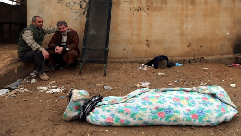 An Iraqi man mourns near the body of his son, who was killed during clashes with ISIL in Mosul [Mohammed Salem/Reuters]