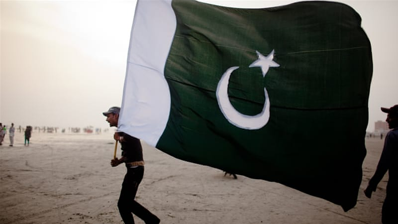 A man walks with a Pakistan National flag, as people gather at Seaview waterfront to celebrate Pakistan's Independence Day on August 14, 2011 in Karachi, Pakistan [Getty]