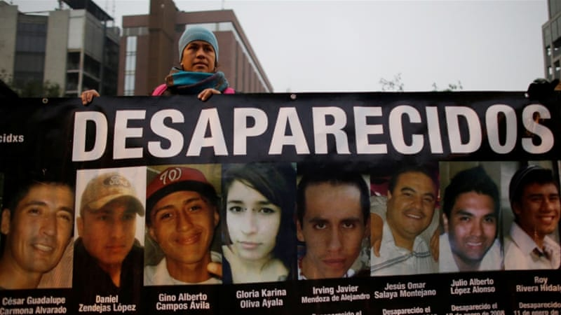 A demonstrator holds a banner with images of missing people during a demonstration demanding justice for the victims of violence, in Monterrey, Mexico [Reuters]