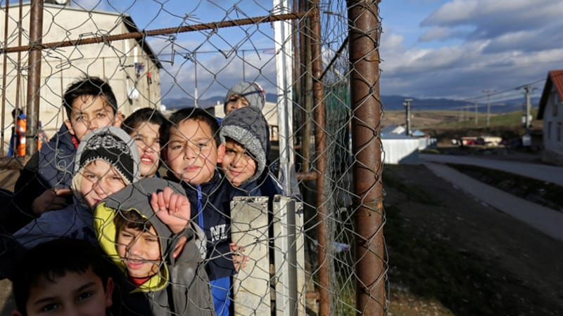 "Roma children stand behind a fence near the so called ""Sheffield Square"" in the town of Bystrany, Slovakia [Reuters]"