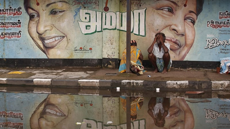 A flood-affected couple sits along a flooded roadside under a picture of Jayalalithaa Jayaram, chief minister of the southern Indian state of Tamil Nadu, on December 6 [Reuters]