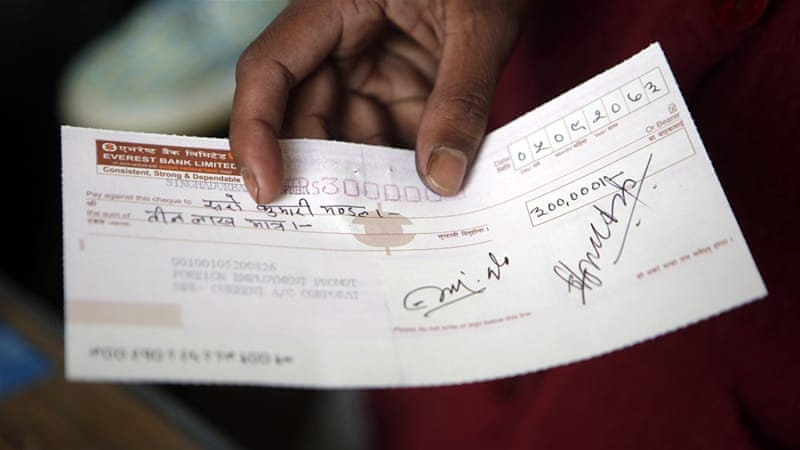 A widow holds a compensation cheque she received from Nepali authorities after her husband died of a cardiac arrest in Qatar [AP]