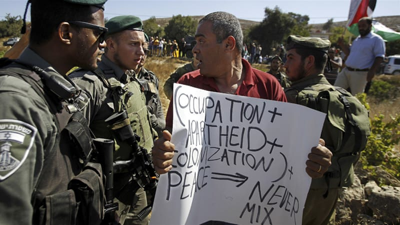 Palestinian protesters argue with Israeli soldiers during a protest against settlement construction [File: Abed al-Hashlamoni/EPA]