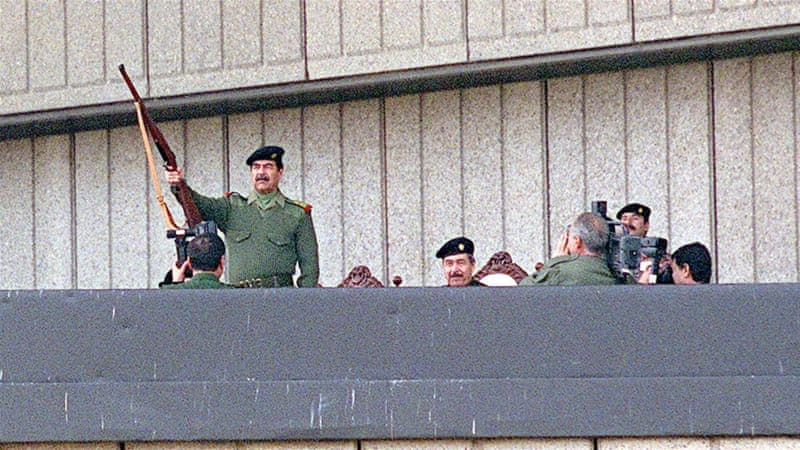 Saddam Hussein raises his rifle in a salute and fires it in November 2000, during Grand Day of Quds festivities in Baghdad [Getty Images]