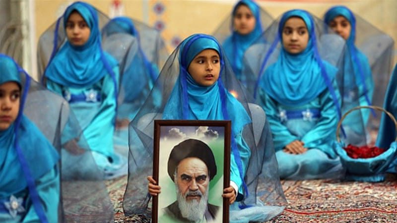 A young Iranian girl holds a portrait of the founder of Iran's Islamic Republic, Ayatollah Ruhollah Khomeini [AFP]