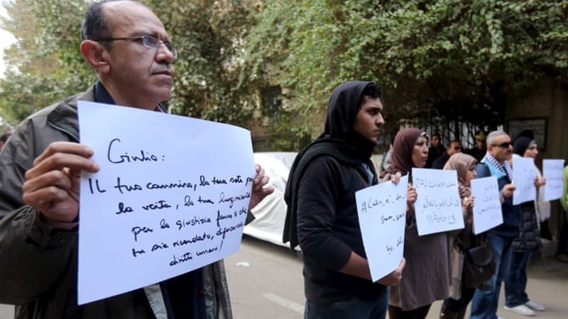 "Activists hold placards that read, among other things, ""Giulio, one of us and killed like us"", during a memorial for Regeni outside the Italian embassy in Cairo [Reuters]"