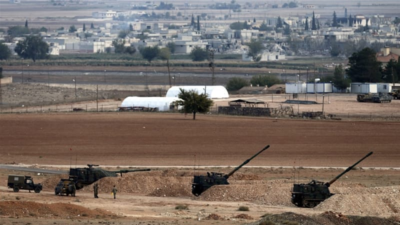 Turkish army howitzers stand in firing position as they guard near the Turkish-Syrian border close to the Suruc district in Sanliurfa [EPA]