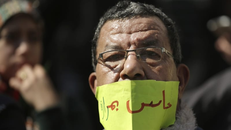 An Egyptian doctor covers his mouth during a protest against rampant police abuses in Cairo, Egypt [AP]