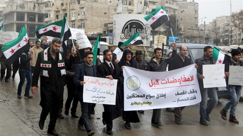 Residents carry banners and opposition flags as they march during a protest in Aleppo [Abdalrhman Ismail/Reuters]