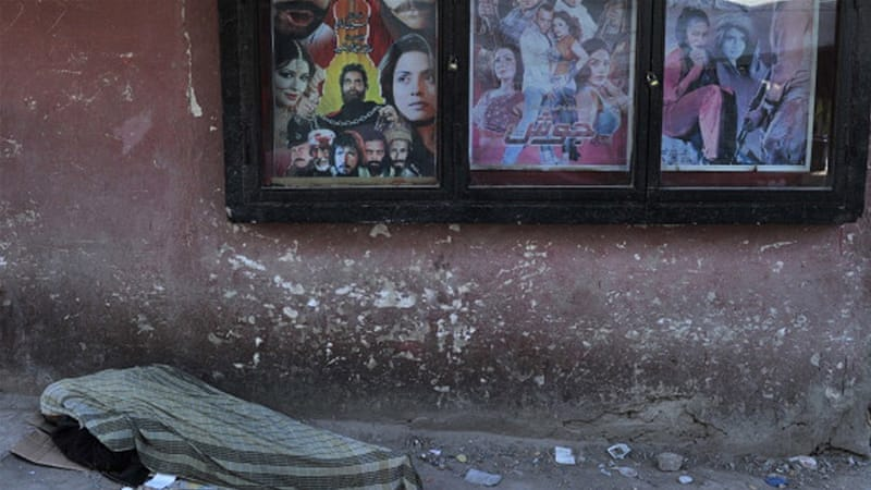 An Afghan man rests near a cinema in Kabul [AFP]