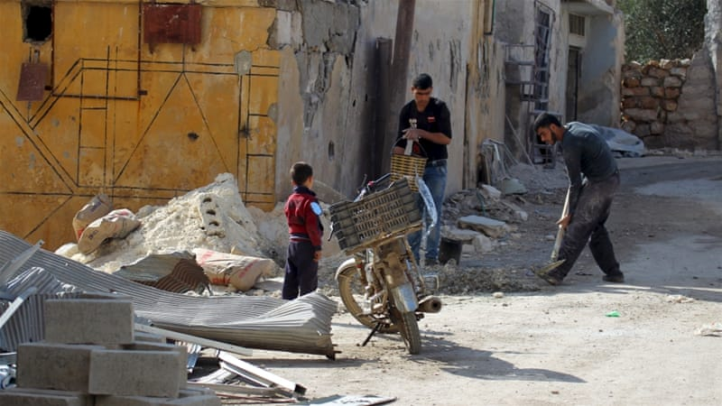 Residents work on fixing a house in the town of Darat Izza, province of Aleppo on Sunday [Reuters]