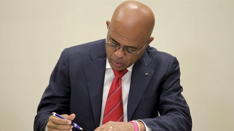 Haiti's president Michel Martelly signs the agreement for an interim government as he steps down [Andres Martinez Casares/Reuters]