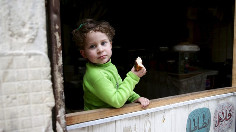 A Syrian child eats bread as she stands in front of a shop in Qaboun neighbourhood of Damascus, Syria [Reuters]