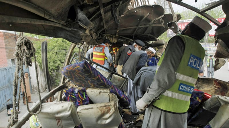 Pakistani security staff examine the bus following a blast in Peshawar on Wednesday [Mohammad Sajjad/AP]