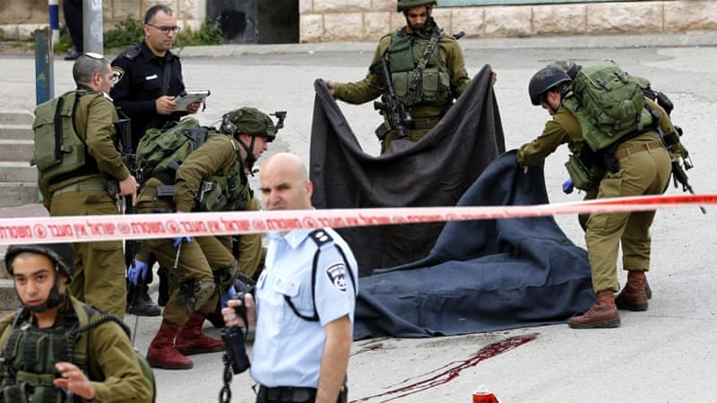 Israeli soldiers cover the body of Abed al-Fattah Yusri al-Sharif at the scene of a shooting in Tal Rumaida in the West Bank city of Hebron. [EPA]
