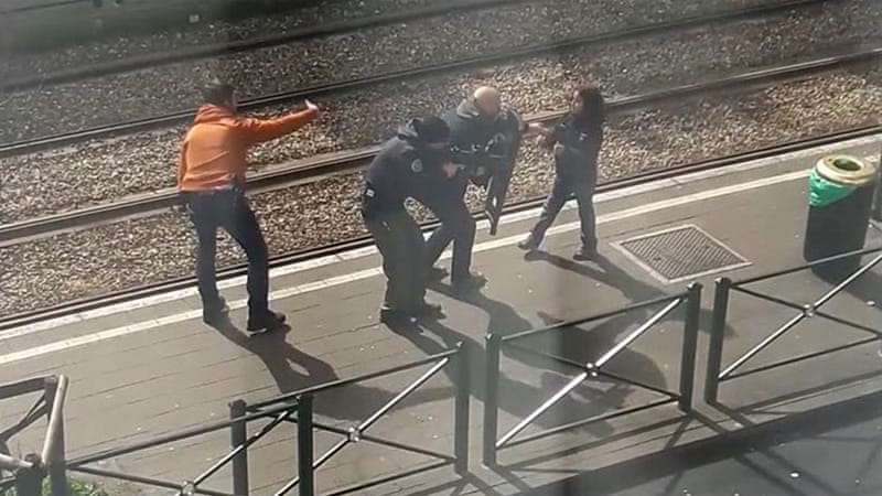 An image showing police as they coax a young girl away from a suspect laying on the ground at a tram stop in Brussels on Friday [AP]