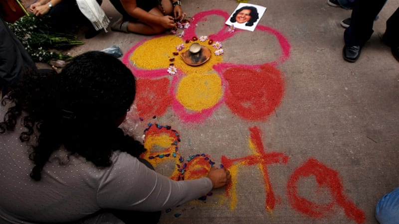 Activists draw a flower on the floor for environmental rights activist Berta Caceres [Jorge Cabrera /Reuters]