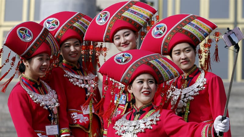 Women wearing ethnic minority costumes take selfies outside the Great Hall of the People [Aly Song/Reuters]