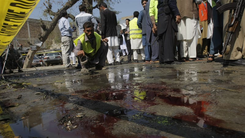 A volunteer surveys the blood-soaked pavement after the deadly suicide attack in Charsadda. [Mohammad Sajjad/AP]