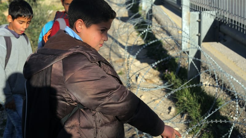 Mohammed Sabah, 10, says the barbed wire often catches on the skin and clothing of children walking by [Abed al-Qaisi/Al Jazeera]
