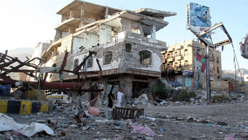 People walk past a building destroyed during recent fighting in Yemen's southwestern city of Taiz March [File photo: Anees Mahyoub/Reuters]