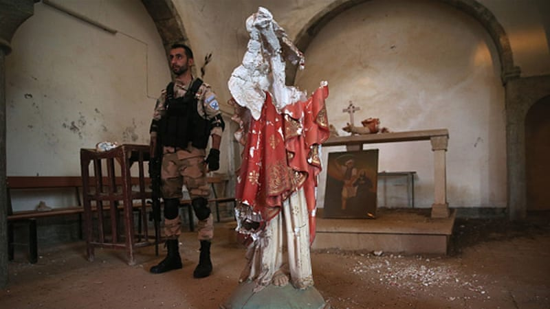A Christian militiaman stands near the broken body of a statue of Christ in a 13th-century church in northern Iraq [Getty]