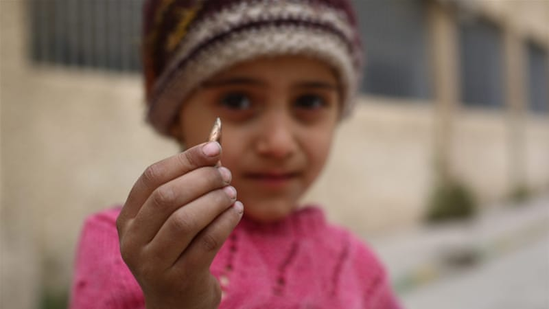 A girl shows a sniper bullet that was found in the school yard in the rebel-held city of Douma, on the outskirts of Damascus, Syria [EPA]