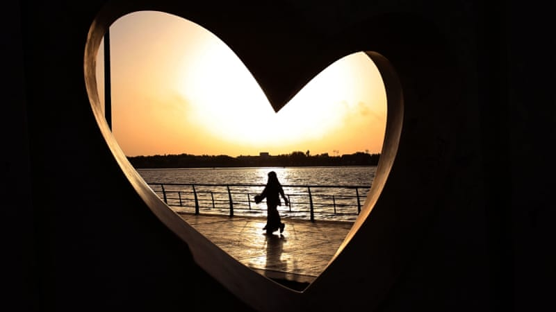 A Saudi woman seen through a heart-shaped statue walks along an inlet of the Red Sea in Jeddah, Saudi Arabia [AP]