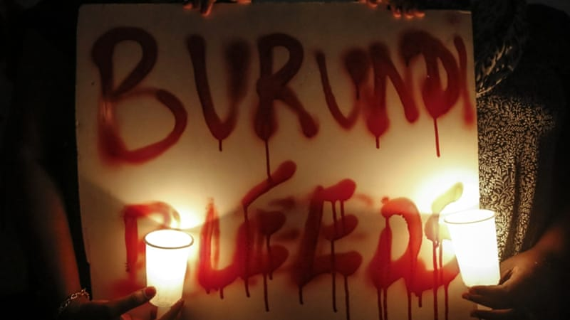 Activists hold candles and a placard reading 'Burundi bleeds' during a candlelit vigil held for Burundi in Nairobi, Kenya [EPA]