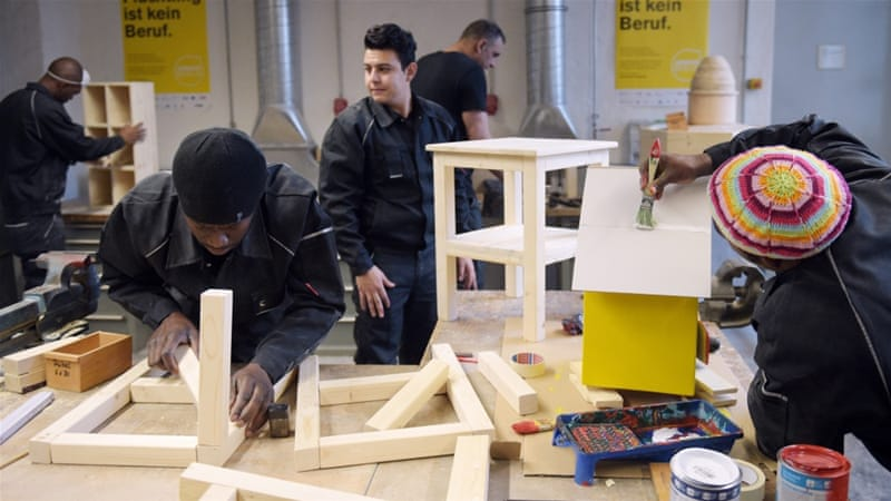 Refugees work in a carpentry workshop, part of the Berlin Chamber of Trades refugee initiative 'Arrivo' in Berlin [Rainer Jensen/EPA]
