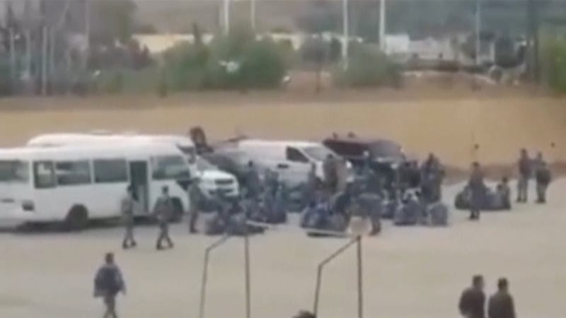 An image taken from a video uploaded on a social media website shows what it says are government security forces walking outside Hama prison [Reuters]