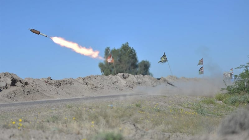 Iraqi fighters fire a rocket towards ISIL positions on the outskirts of Fallujah [Reuters]