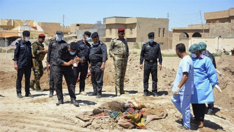 Iraqi security forces and a forensics team at a mass grave for ISIL victims in Ramadi, Iraq [AP]